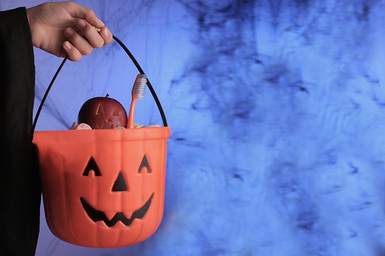 Trick or treating for healthier options. In the bucket there is an apple and a toothbrush.