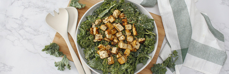 A Kale salad with Tahini Vinaigrette dressing with fried tofu.