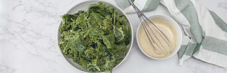Kale and dressing sitting next to each other.