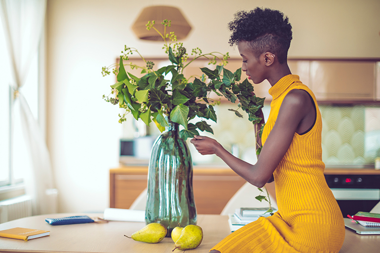 Woman fixes flowers in a modern kitchen with lots of yellows in it.