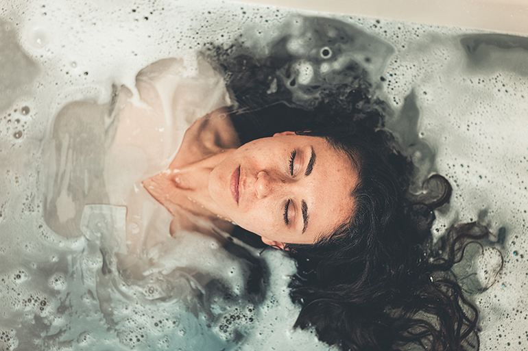 A woman takes a bath with her shirt on while meditating.