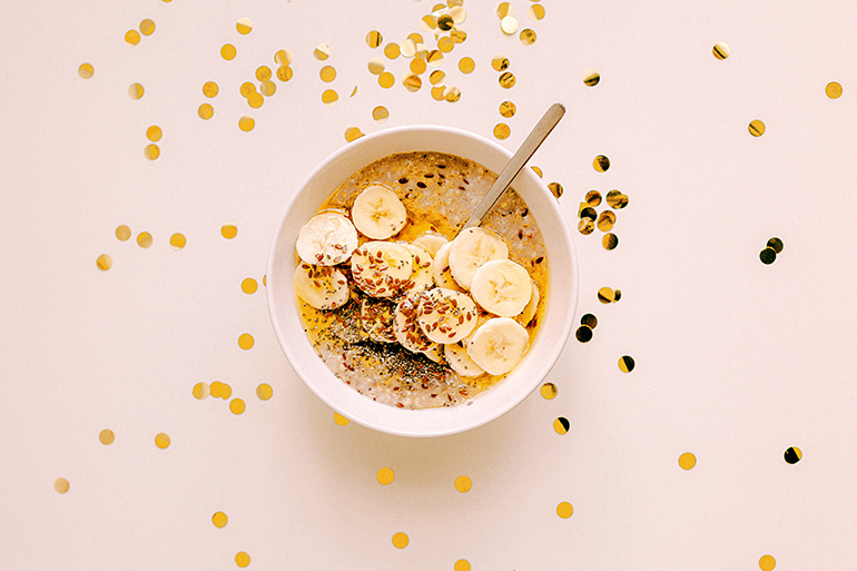 A delicious smoothie bowl with bananas sits on a counter of confetti.