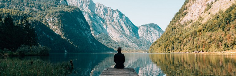 Person meditating on the end of a doc. The mountains are in the background and the water is so calm it is reflecting their image.