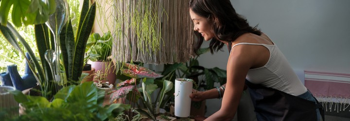A woman is watering her plants and checking their water levels.