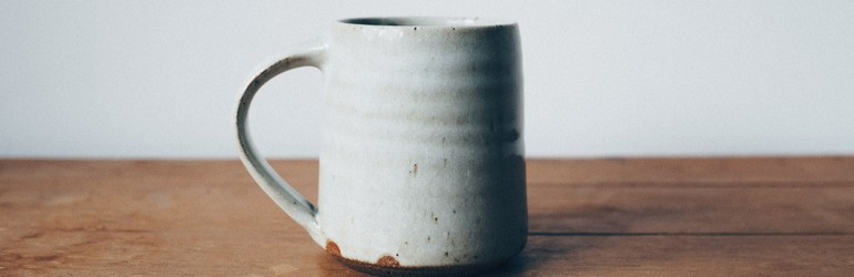 A pottery mug sits on a table.