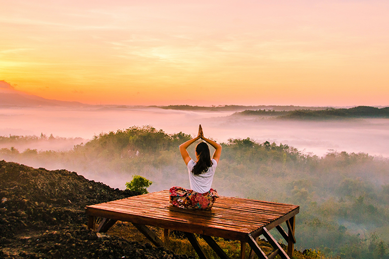 A woman meditates on a hillside while the sun rises in the distance.