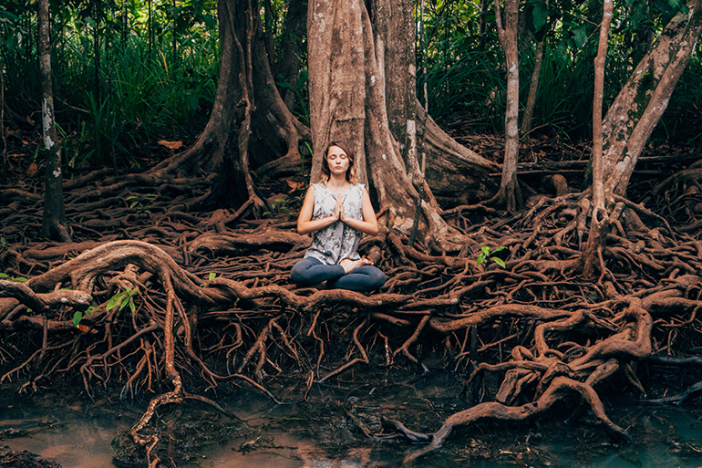 Woman meditating for her root chakra on some tree roots.
