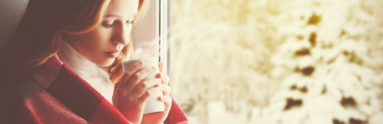 A blonde woman stands by a window and stares a a cup of tea that she is holding in both of her hands.
