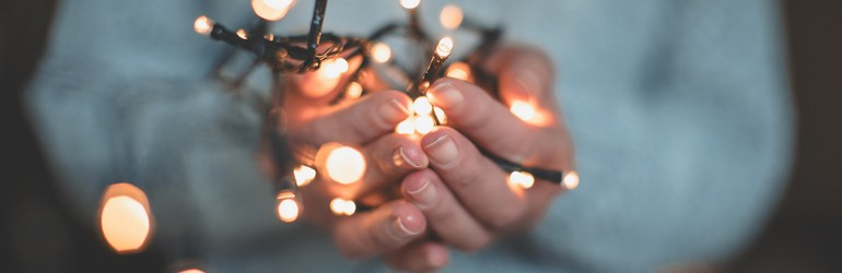 Person wearing blue sweater holds fairy lights out in their hands towards the camera.
