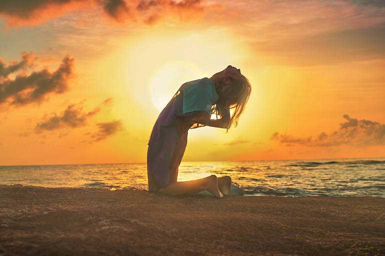 A woman leans backwards while meditating on a beach at sunset. She holds her back.