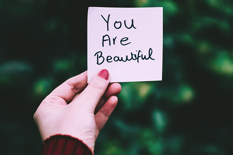 "Woman holds sticky-note that says ""You are beautiful"" on it."