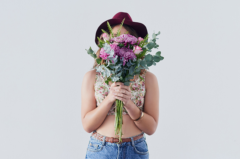 A person wearing a summery outfit with a brown hat. She holds a large bouquet of flowers in front of her face.