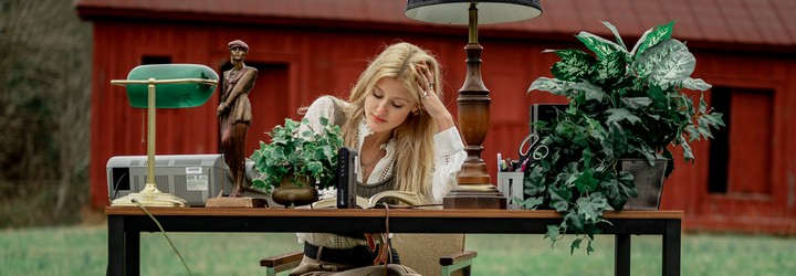 A woman is thinking at a desk in a field.