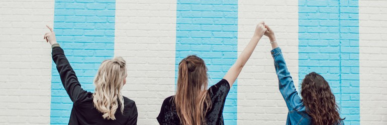 Three friends hold hands in front of a blue and white striped wall.