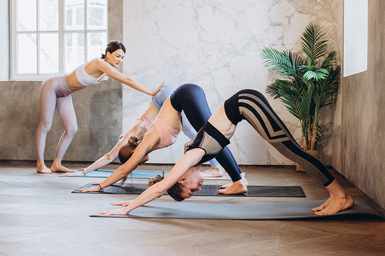 Two people doing yoga with an instructor making corrections.