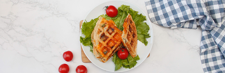 A cheesy stuffed waffle on a plate next to some tomatoes.