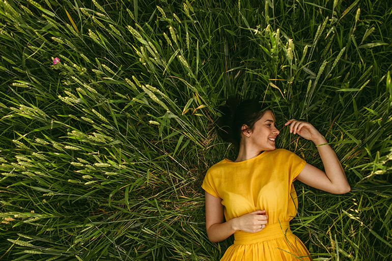 A woman in yellow lays on beautiful green grass.