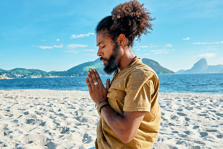 A man meditates with his hands at hearts center in a dessert scene. He is surrounded by sand.
