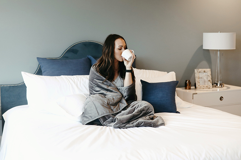 Woman drinking tea under a blanket.