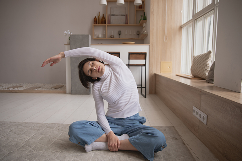 A woman practices yoga in her home with her eyes closed.
