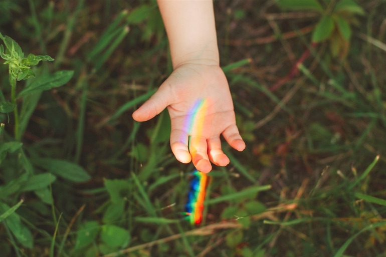 A person puts their hand out to catch a refracted light rainbow against some tree leaves.