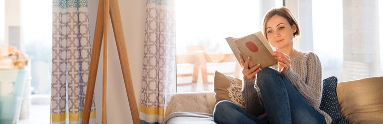 Woman reading a book in her living room.