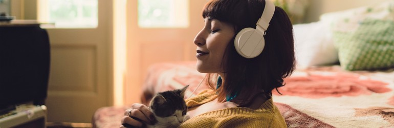 Woman listening to music and breathing deeply while holding a cat.