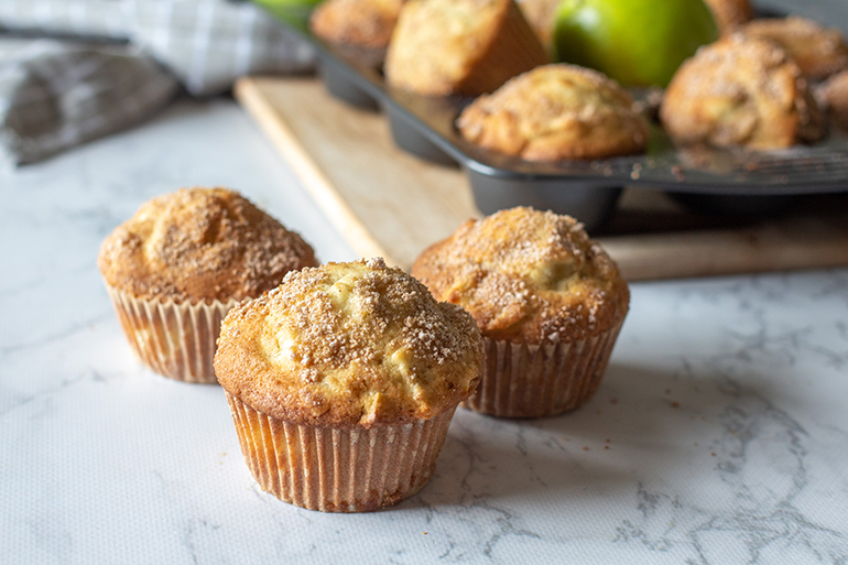 Apple strudel muffins sitting on a white marble counter in front of a muffin tray.