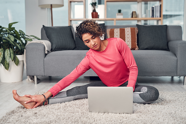 Woman working out at home in front of her laptop.