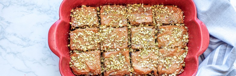 Baked baklava in a baking sheet, cut up for serving.