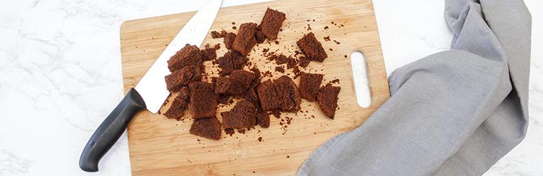Chopped up dark chocolate on a wood cutting board.