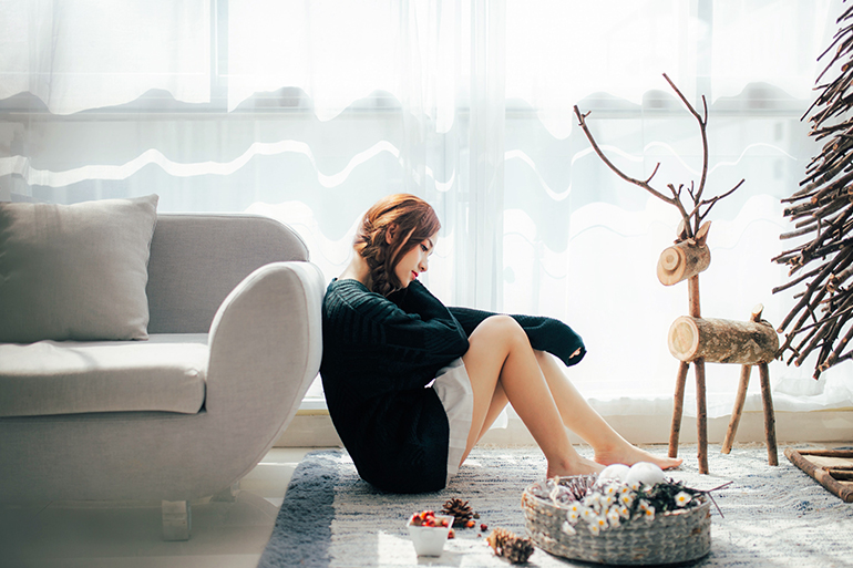 A woman looks sadly at holiday decorations, she is alone.