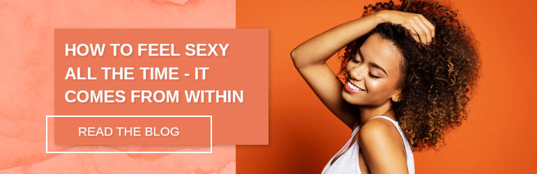 This image is linked to an article. Read next: How to Feel Sexy All The Time - It Comes From Within, the image is of a woman smiling and running her hand through her hair. The background is orange.
