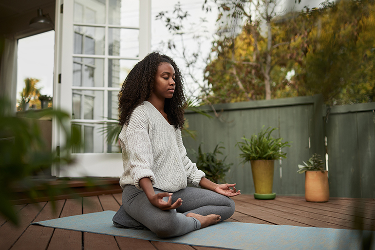A woman sits on her deck meditating on a yoga mat.