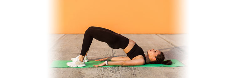 A beginner backbend where the person is attempting a bridge pose with their shoulders stabilized on the yoga mat.