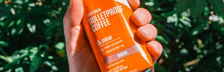 A bullet proof coffee is a carton as an example of the keto diet. It is an orange carton and a person is holding it in front of some green bushes. They have tattoos on their arm.