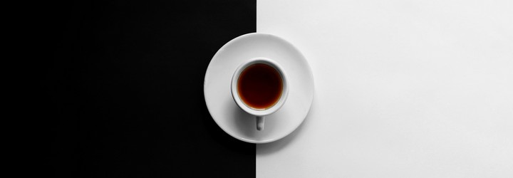 A cup of coffee on a back and white background.