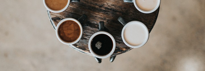 Cups of coffee with different amounts of milk in them on a lazy susan.