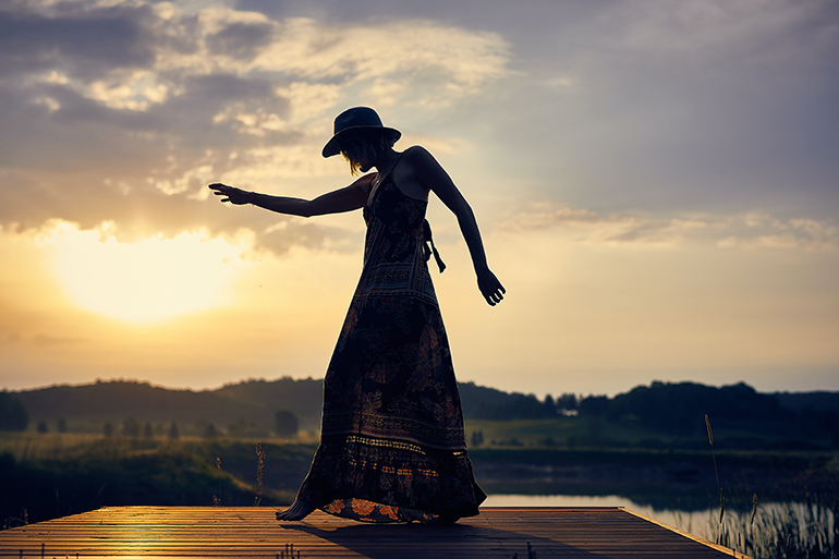 A person in a big floppy hat and maxi-dress dancing on a lake dock in front of the sunset.
