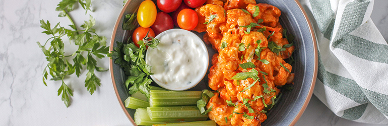 A close-up of vegetarian buffalo cauliflower wings in a bowl.