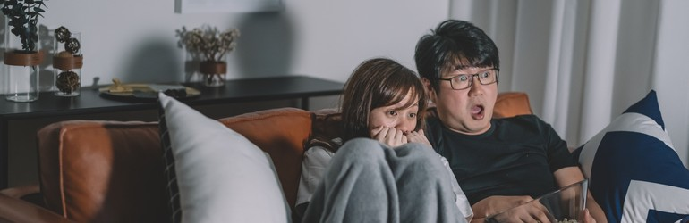 A couple watches a scary movie on Halloween wrapped up in a blanket on their couch.