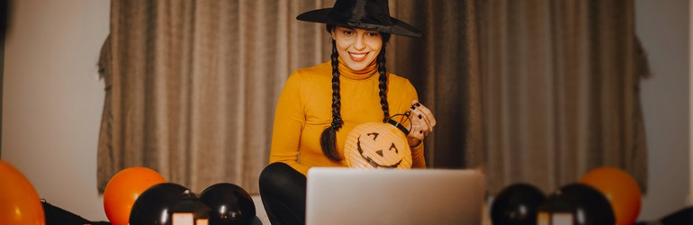 A woman having a costume contest while video chatting with friends on Halloween.