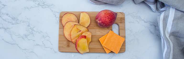 Fruit and cheese on a cutting board.