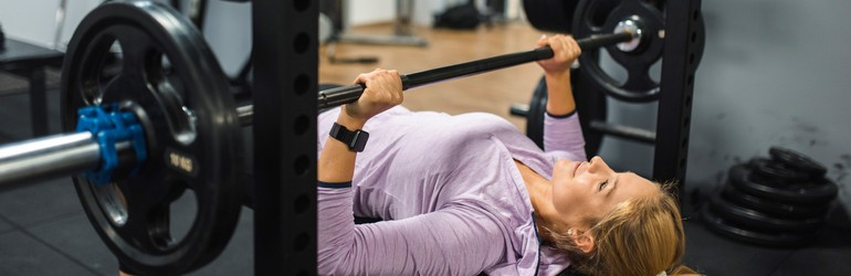 A woman lays down on a bench and does a laying chest press with a barbell.