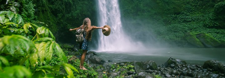A person in nature next to a waterfall with her arms out. She is surrounded in lush green jungle.