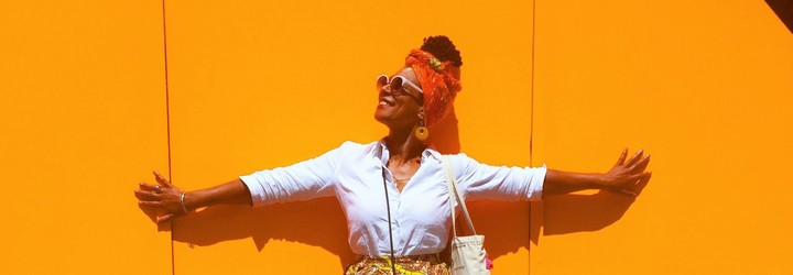 A woman stands with her arms spread out against an orange feature wall. She is basking in the bright sun as looks up to the left of the frame while wearing an orange head scarf and skirt.