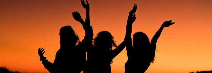 Three silhouetted women dance in front of an orange sunset.