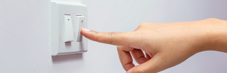 A person's hand is turning off a light switch.