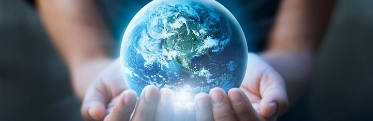 There are two hands of a woman in the image and she is holding a 3D rendering of the earth out towards us.