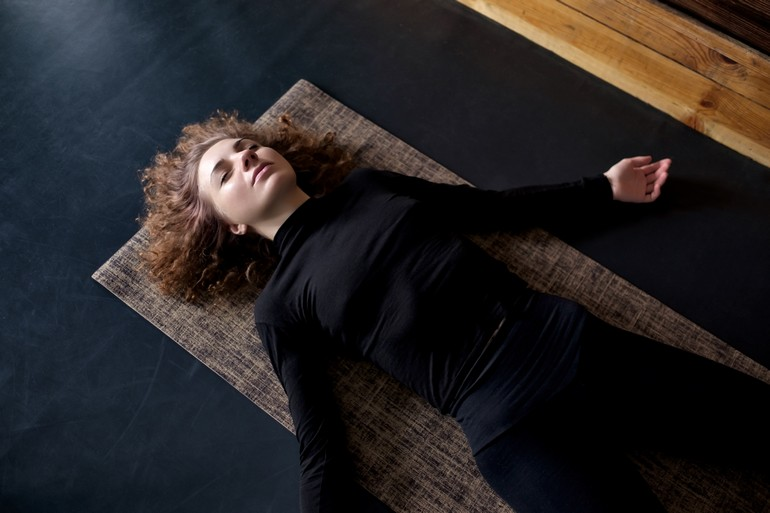 A woman wearing all black is in corpse pose.